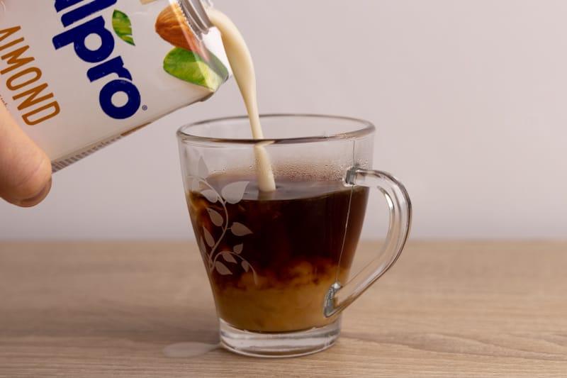 Adding almond milk to coffee