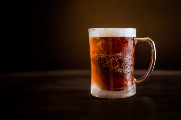Cold beer in a clear glass mug