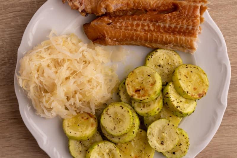 Cooked zucchini, sauerkraut and smoked fish