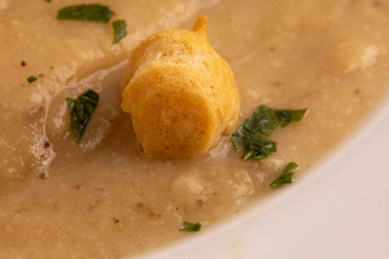 Creamy cauliflower soup garnished with soup pearls