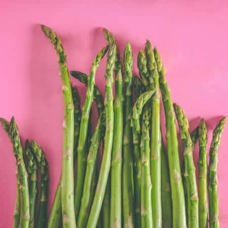 Green asparagus on pink background