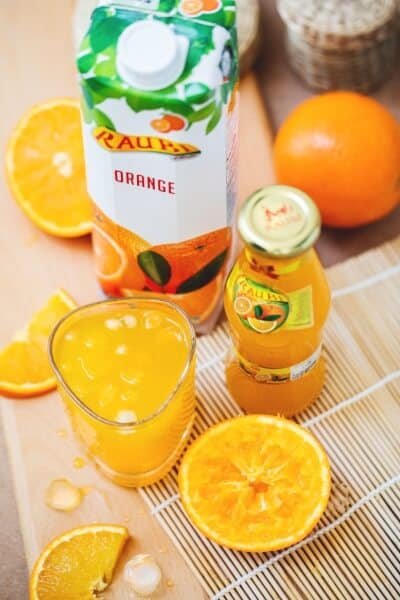 A glass of fresh orange juice and a bottle