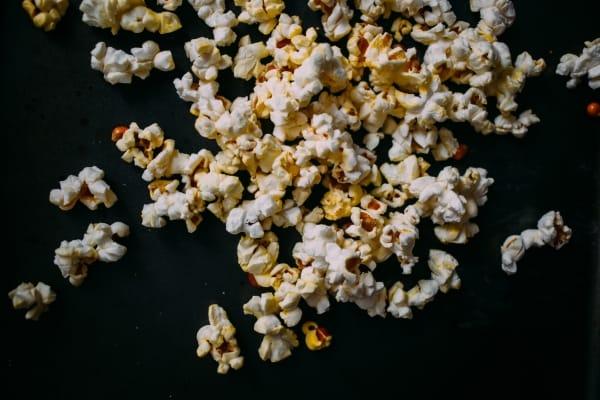 Popped popcorn on black surface