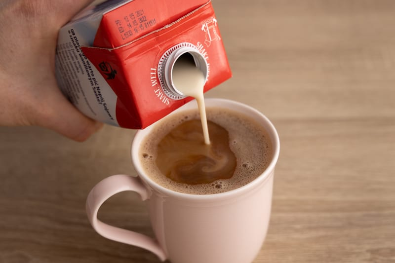 Pouring soy milk in coffee