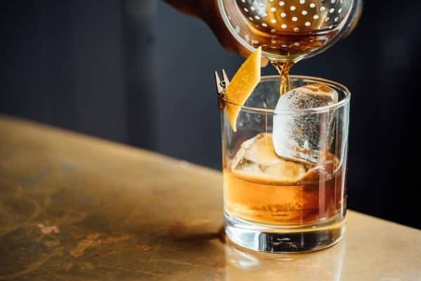 Pouring whiskey on ice cubes