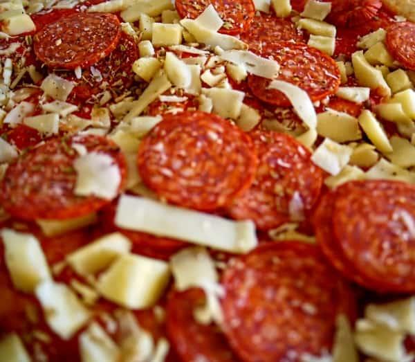 Preparing pepperoni pizza