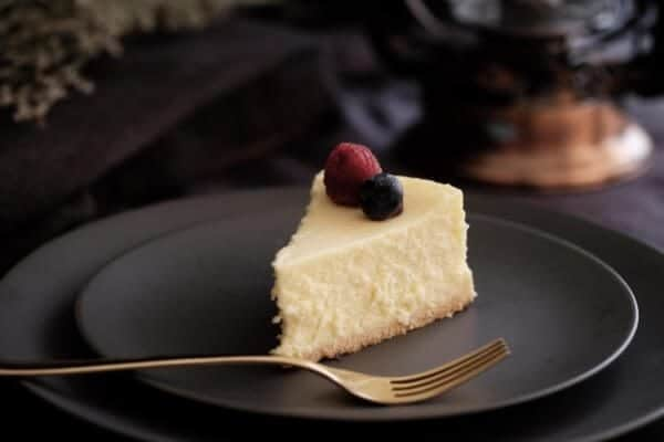 Slice of cheesecake on a black plate