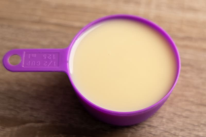 Sweetened condensed milk in a measuring cup