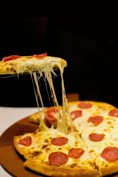 Taking a slice of pepperoni pizza