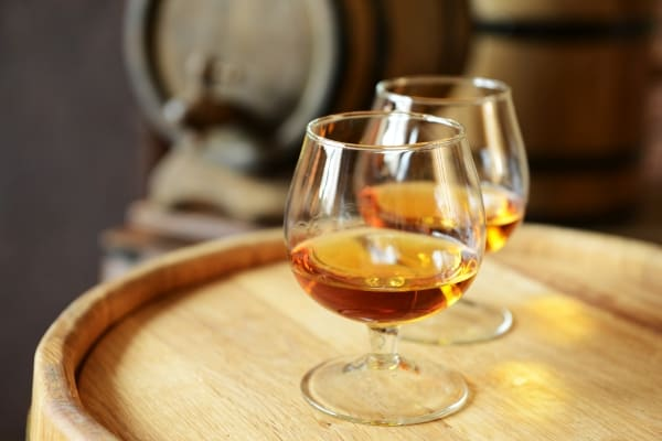 Two glasses of brandy in a cellar with old barrels