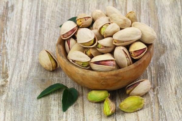Unshelled pistachios in a wooden bowl