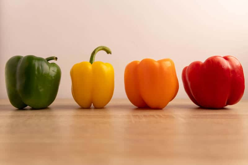 Whole bell peppers: green, yellow, orange, and red