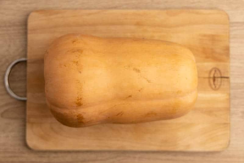 Whole butternut squash on a cutting board